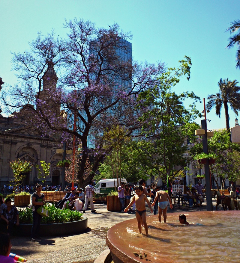 At the center of Plaza de Armas in downtown Santiago, children play in a water fountain dedicated to Simón Bolívar.