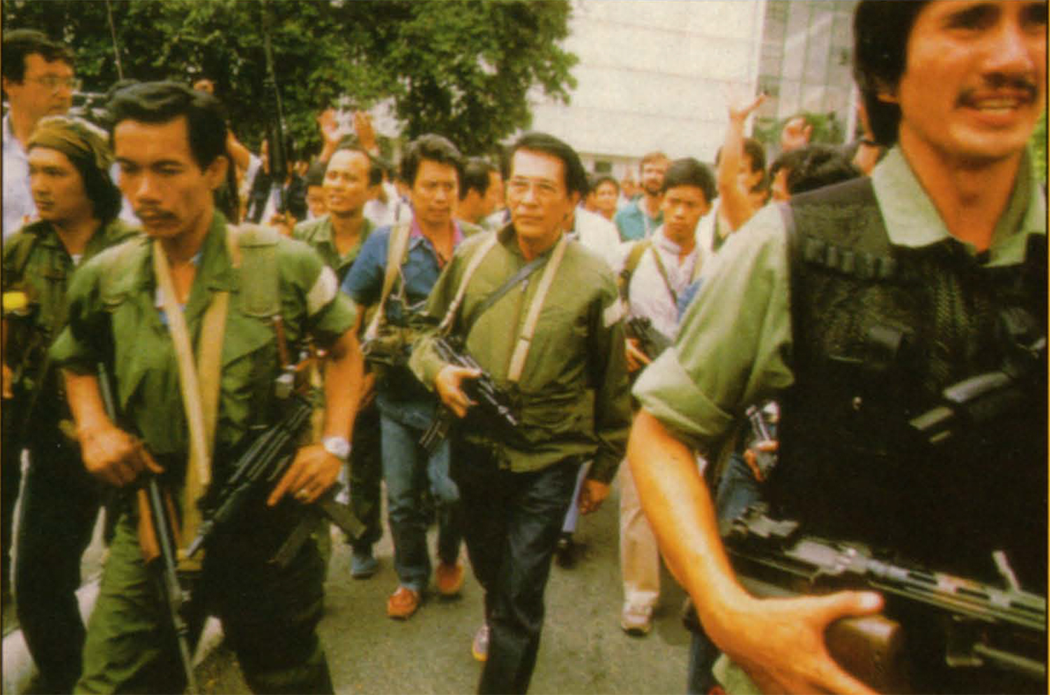 "At midday of February 23, Minister Juan Ponce Enrile and his men left Camp Aguinaldo to join General Fidel Ramos in Camp Crame. RAM leader Col. Gregorio ""Gringo"" Honasan (right foreground) led the pack.  (Photo by Tom Haley)"