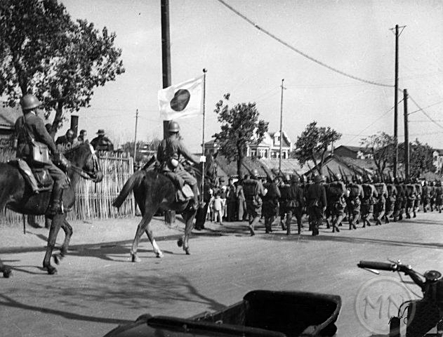Japanese soldiers parade through the streets