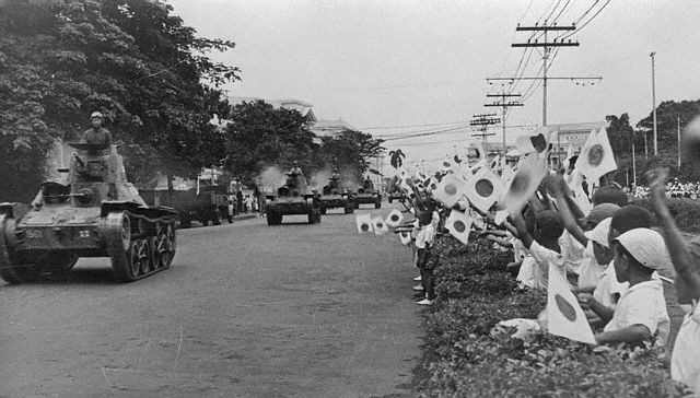 Children waves flags at the Japanese tanks