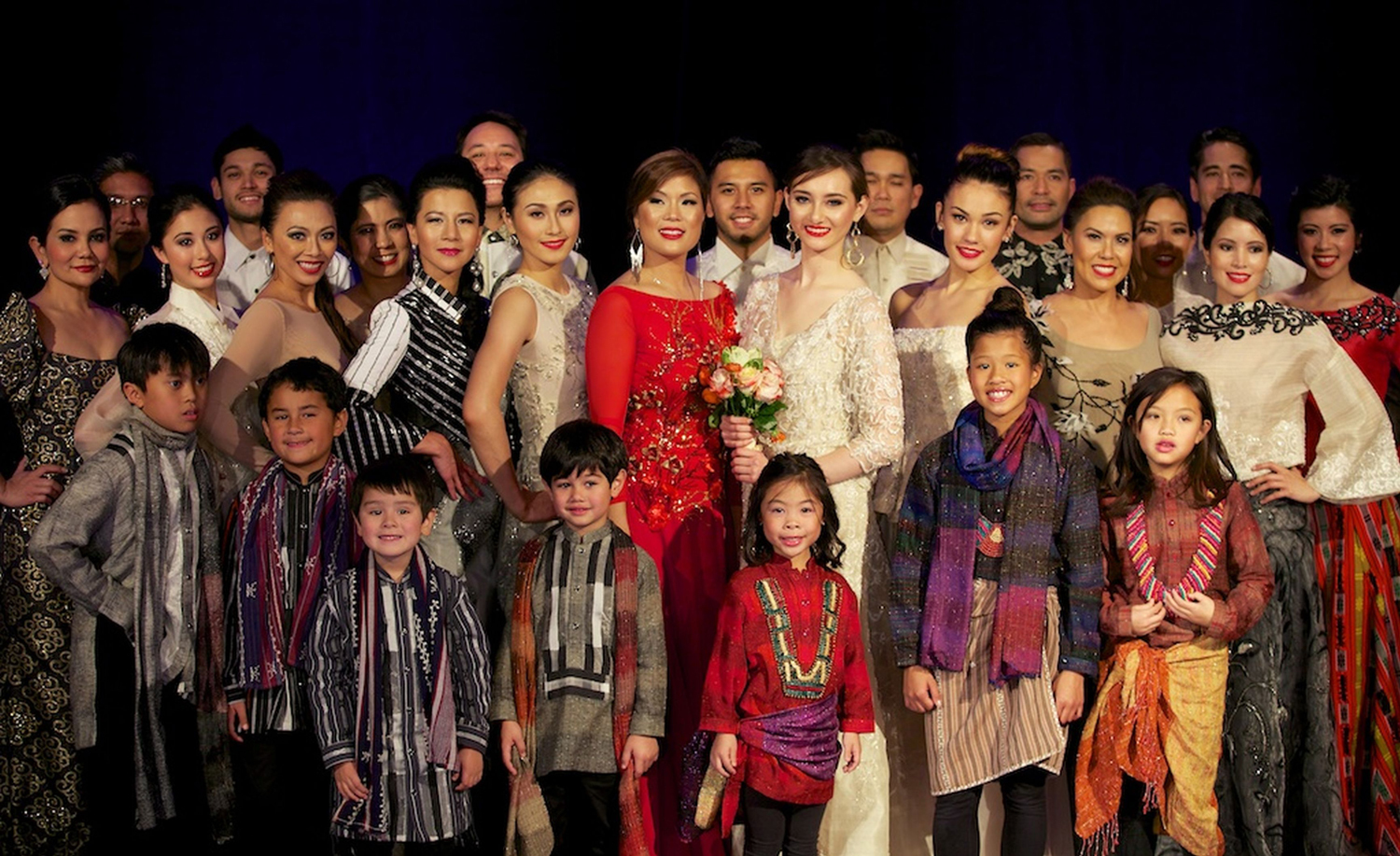 """PIA volunteers at curtain call showing off the various designs of Barge Ramos at the """"Holiday Haute Couture XII"""" fashion show fundraiser  (Photo by iClickforacause.org)"""