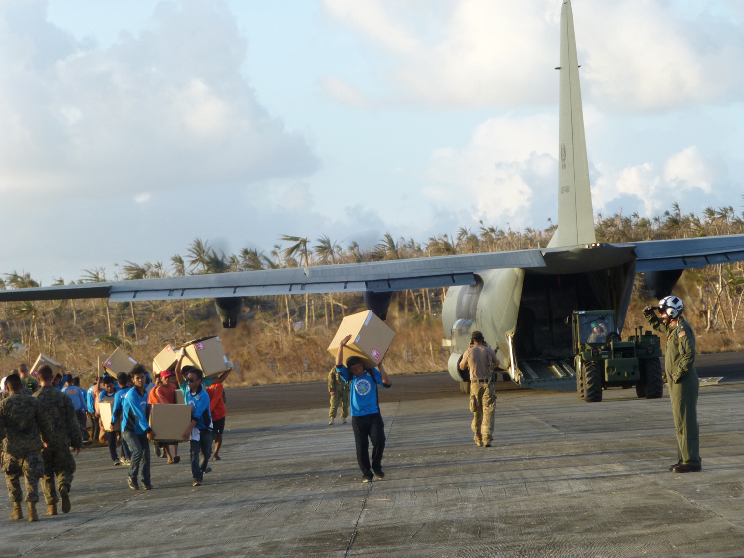 The townspeople of Guiuan, Samar help unload relief goods from a C-130.  (Photo by Criselda Yabes)