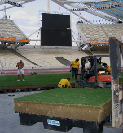 """New turf being laid out at Athens' Olympic stadium in 6,500 4'x4' plastic trays in 2004. Because Greece's soil is rocky, ideal grass soil had to be imported from Sicily. Also, due to a manpower shortage in Greece before the Games, some 45 foreign workers had to be hired as """"soil caretakers and transporters"""" – all in an effort to get Olympic Stadium ready for the athletic competition after the opening ceremony. Note that each plastic tray is individually numbered.  (Photo courtesy of Myles Garcia)"""