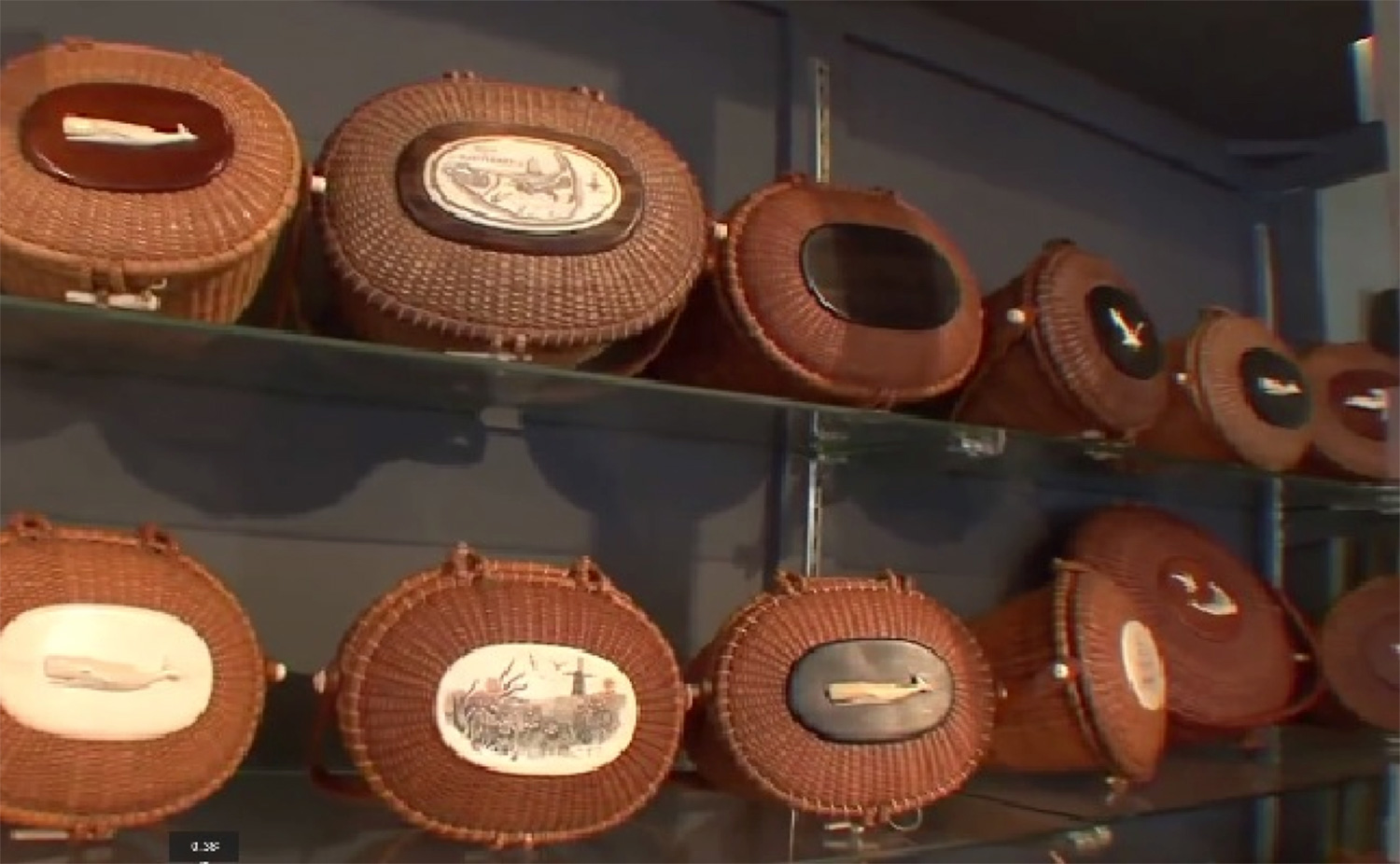 """A selection of authentic and """"in-the-style-of-Jose Reyes"""" baskets at a Nantucket Antiques store. The look is not patented, but Reyes and other basket makers sign or apply labels on their creations. (Photo is a YouTube screen grab from Sylvia Antiques website)"""