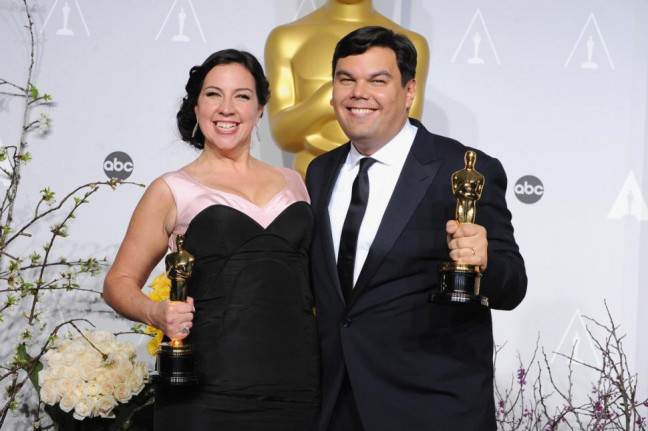 """Robert Lopez (R) with wife and writing partner, Kristen Anderson-Lopez after winning the Oscar for """"Let it Go"""" from """"Frozen."""" (Photo credit: Steve Granitz/WireImage)"""