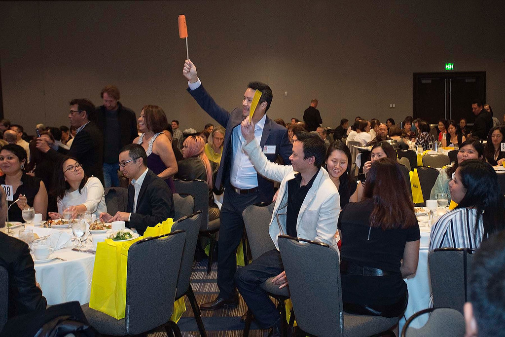 "Furious bidding from guests at PIA's 2015 ""Giving Hope to the Children II"" event for the various generous Live Auction prize packages. This portion raised about $30,000 this year, including 121 new children's educational pledges.  (Photo by Noel Ferrer)"