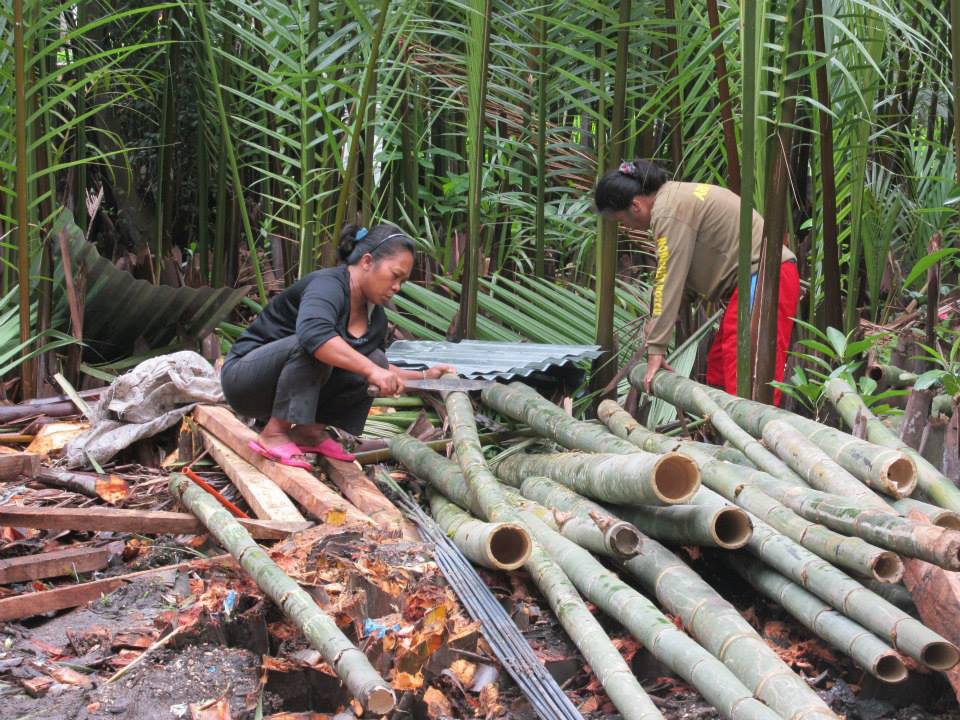 Women preparing the bamboo for construction of a new home.