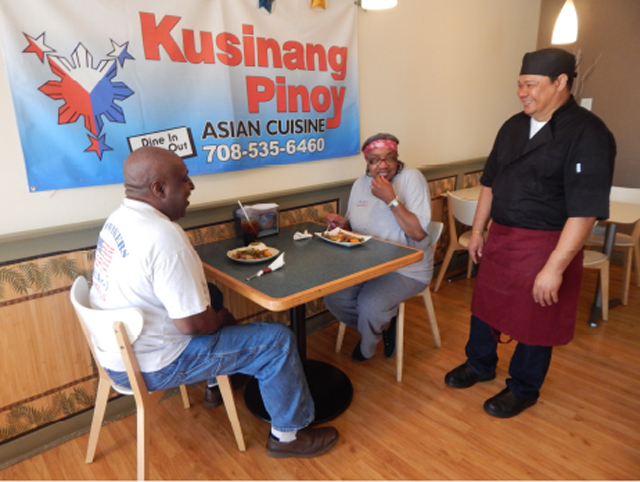Johnny Ventura chats with customers Tommy and Bobbie Ferguson. (Photo by Ivan Kevin Castro)