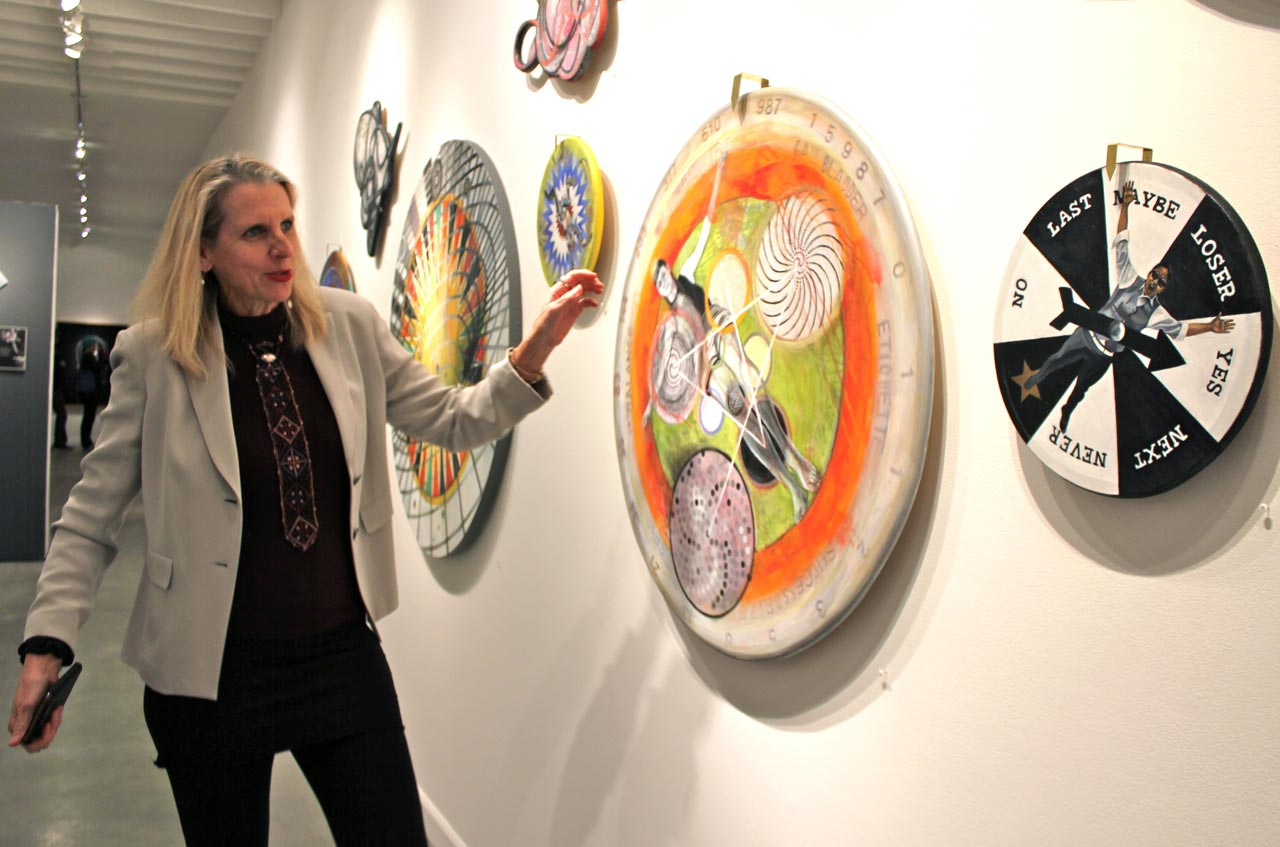 """Johanna Poethig spins a piece at the opening of the Positional Vertigo exhibition. Filipino American imagery is both overt and subtle in her work, as in the inclusion of the words """"Gall Bladder"""" on the wheel (below numbers 15987). Poethig revealed that this refers to a Philippine tribe that gives equivalent importance and mythic status to that organ as we do to the heart. (Photo © France Viana)"""