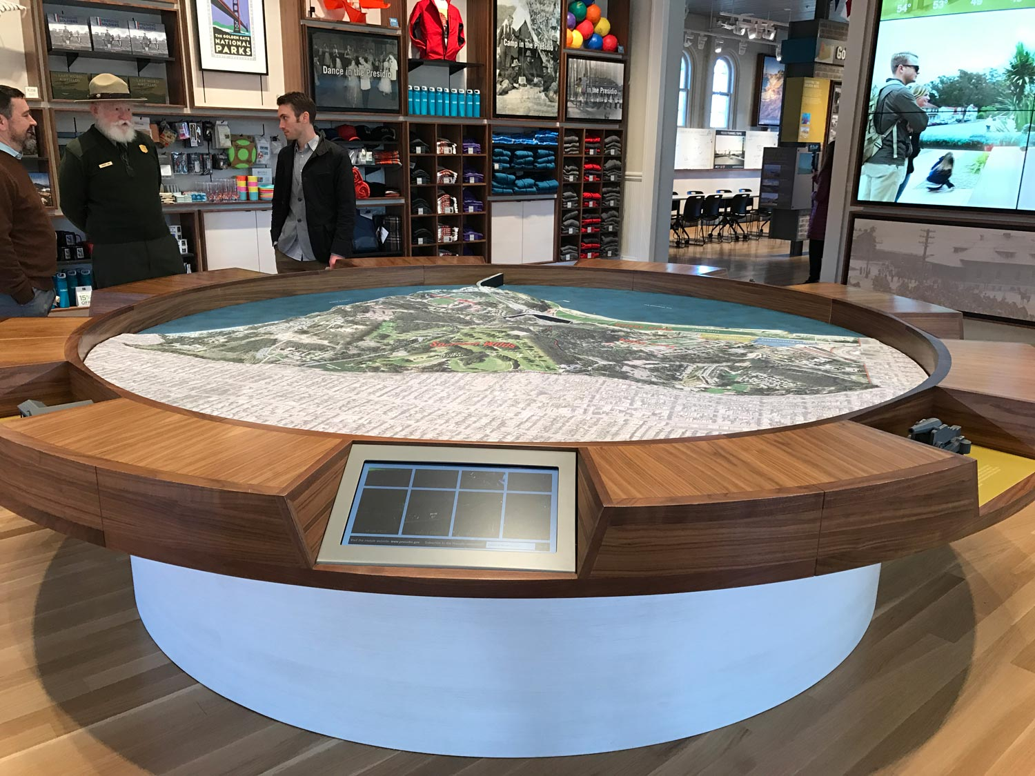 Large-scale Presidio model surrounded by touchscreen panels that help visitors select destinations to visit during their day in the park.