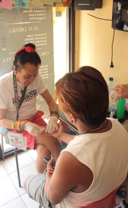 Yabut performing an HIV test on a client (Photo courtesy of Bootz Yabut)