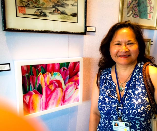 """Nannette Nemenzo with her painting """"Bloom"""" at the UCSF ARTshow in 2016. (Photo courtesy of Nannette Nemenzo)"""