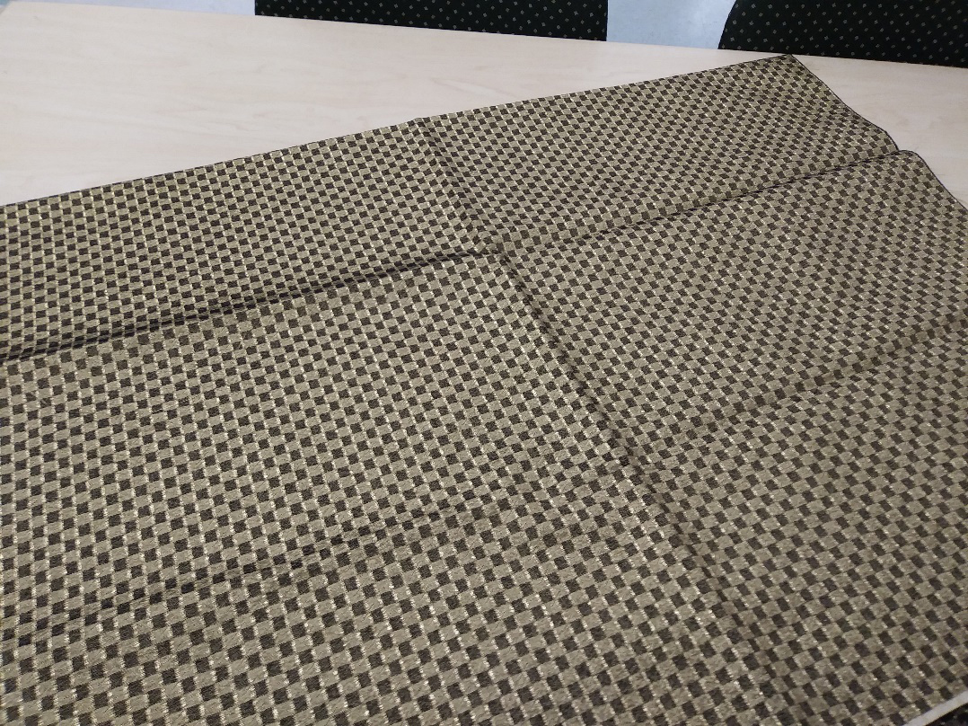 The camera doesn't do the piece of gold fabric justice. How can a flat image capture the feel, thetexture, the warp and woof of an exceptional piece of cloth—a rare fabric on which you somehow see your name invisibly etched?