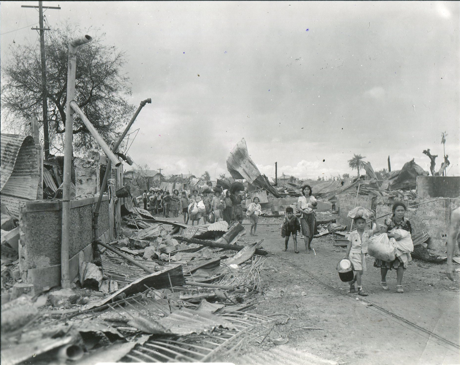 Filipino refugees make their way through the ruined city on February 12, 1945. (National Archives)