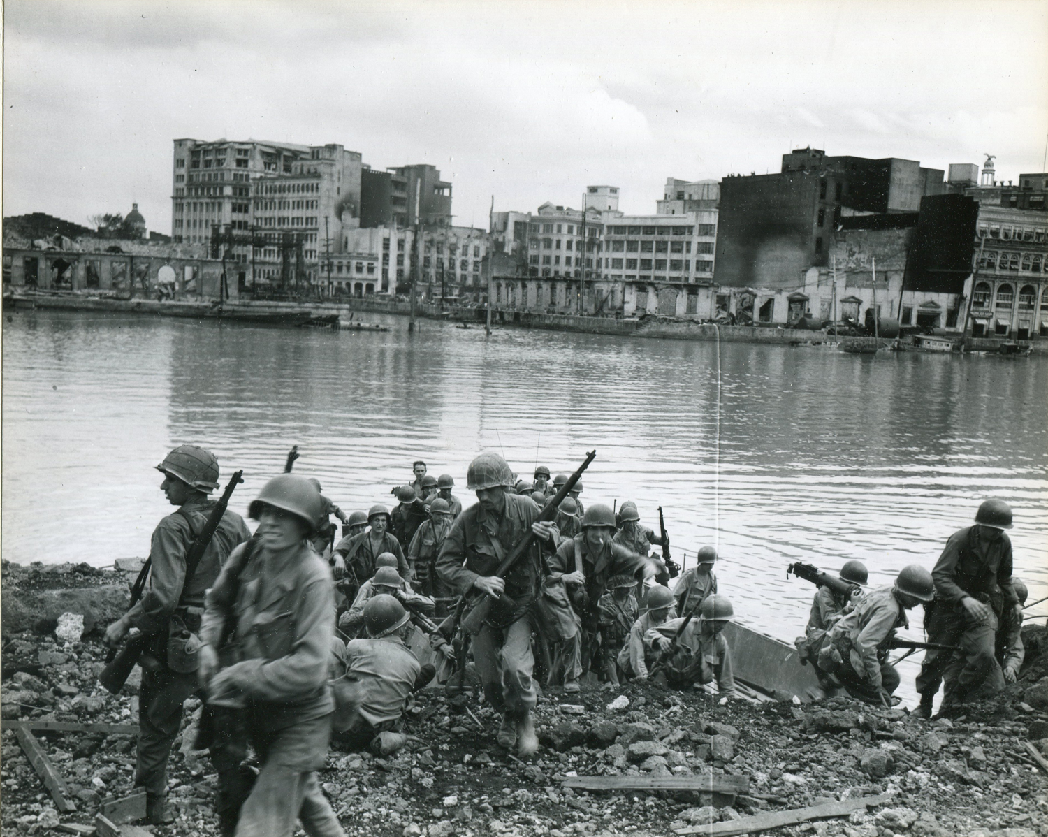 American troops storm the south bank of the Pasig River during the American assault on the Walled City on February 23, 1945. (National Archives)