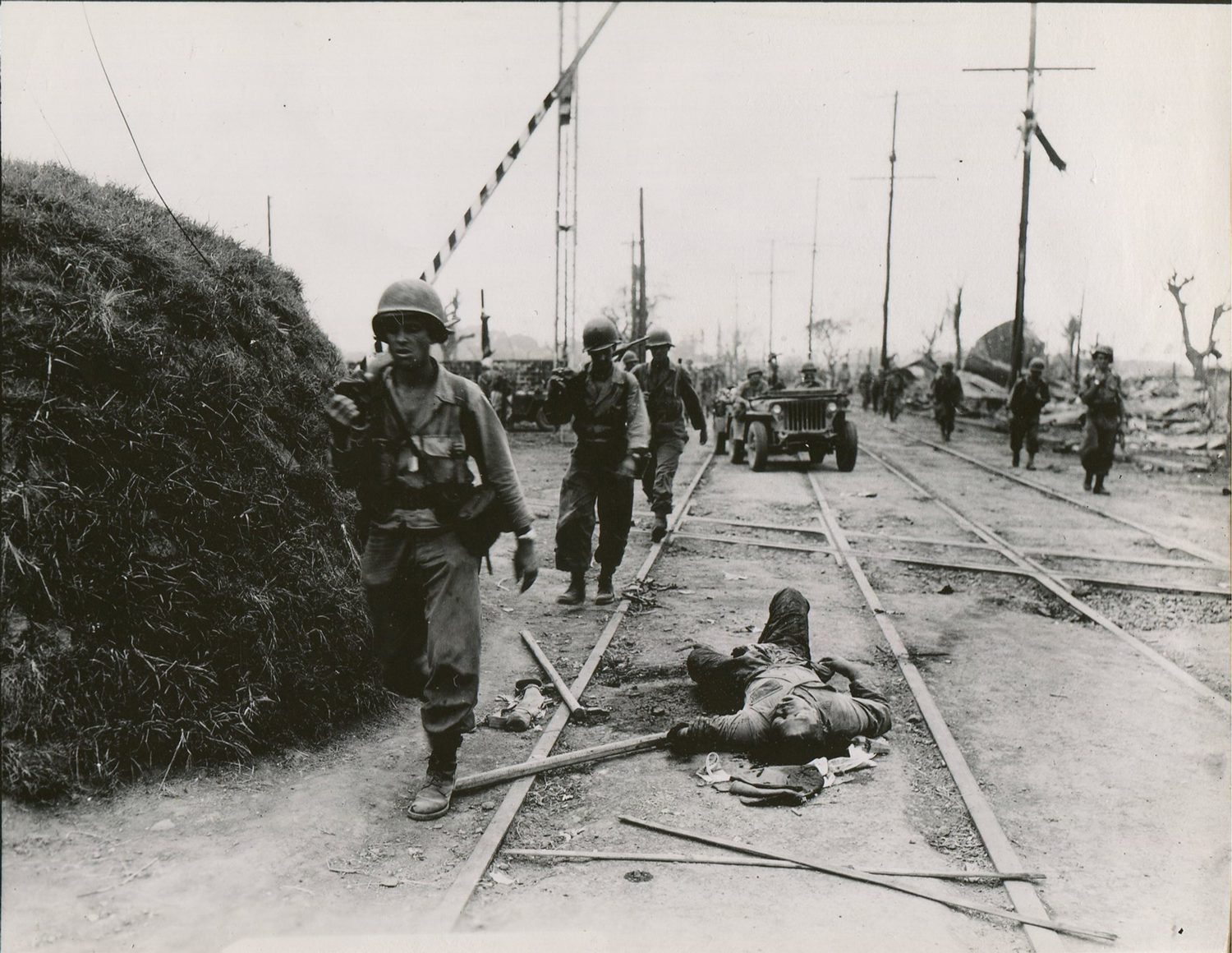 Troops with the First Cavalry Division advance past a dead Japanese soldier sprawled out in the street in the district of Paco on February 12, 1945. (National Archives)
