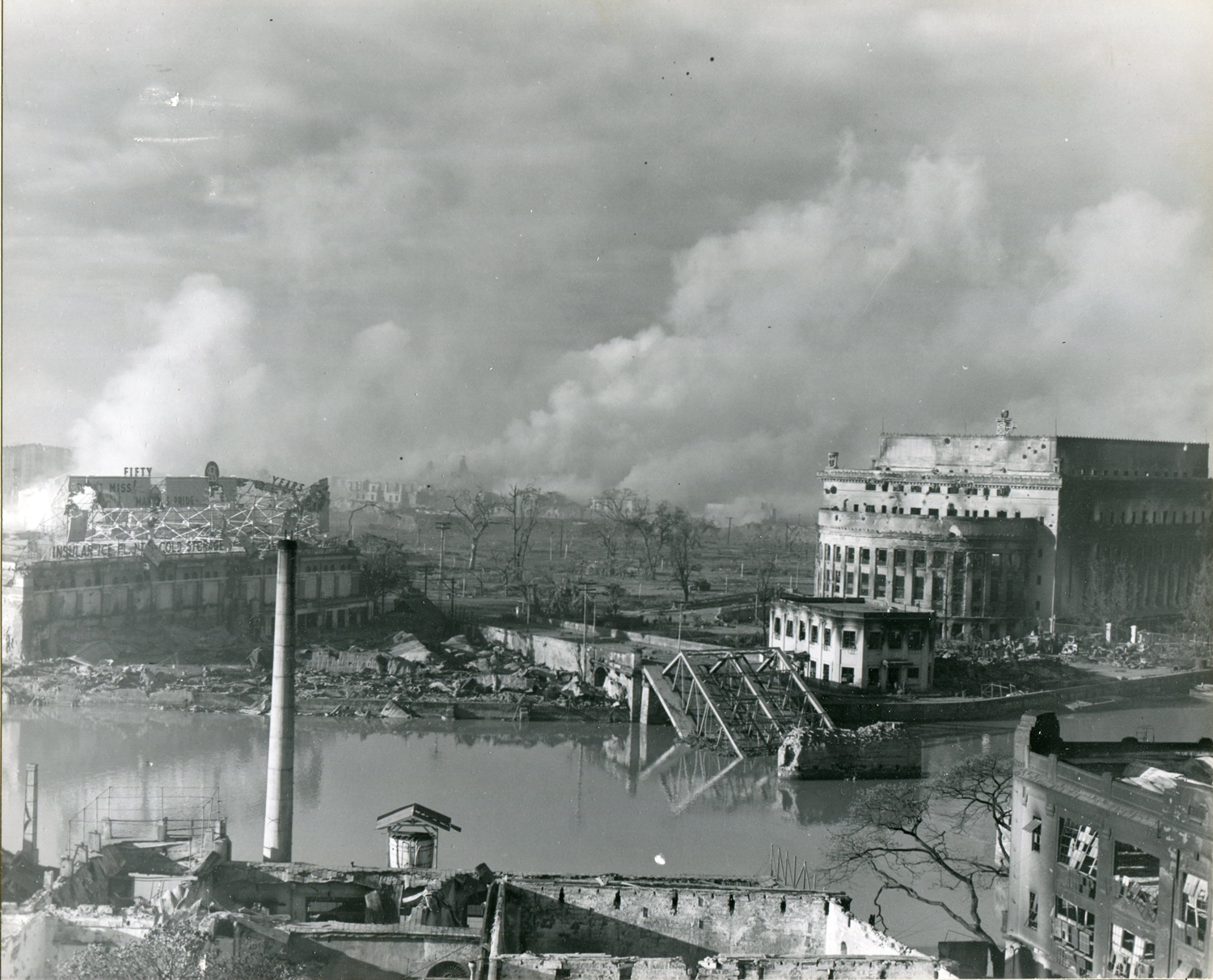 The dark smoke from artillery fire wafts across the ruins of southern Manila on the morning of February 23, 1945, as American troops prepare to assault the Walled City. Pictured on the right are the battered General Post Office and the remains of the Santa Cruz Bridge. (National Archives)