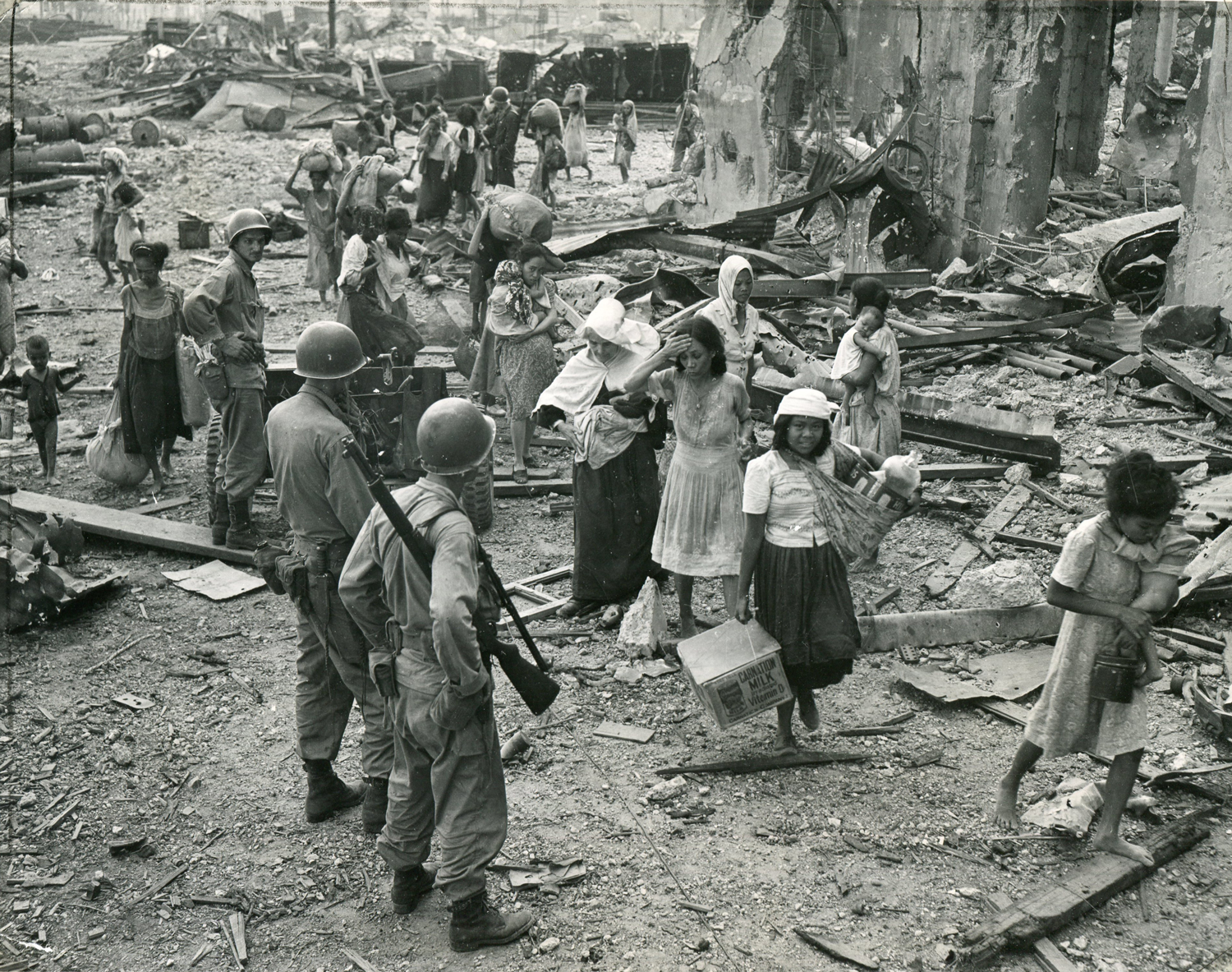 Filipino refugees, many barefoot, pick through the wreckage of north Manila, having just crossed the Pasig River following the fight for the Walled City. The nun carries a motherless infant born just three days earlier. (National Archives)