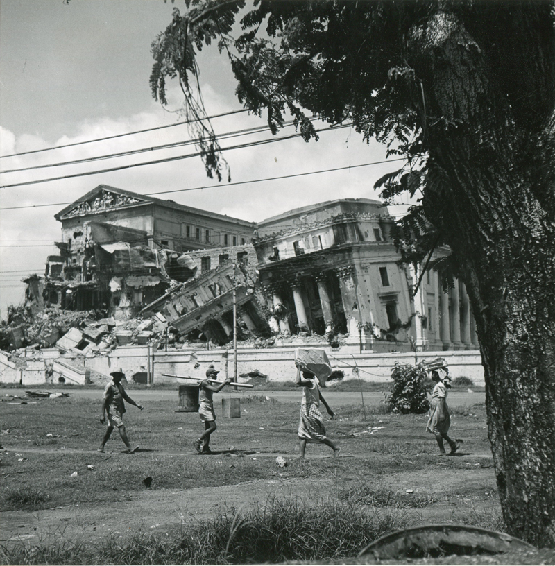 Life goes on as Filipinos walk in front of the ruins of the Philippine Legislature in May 1945. (National Archives)