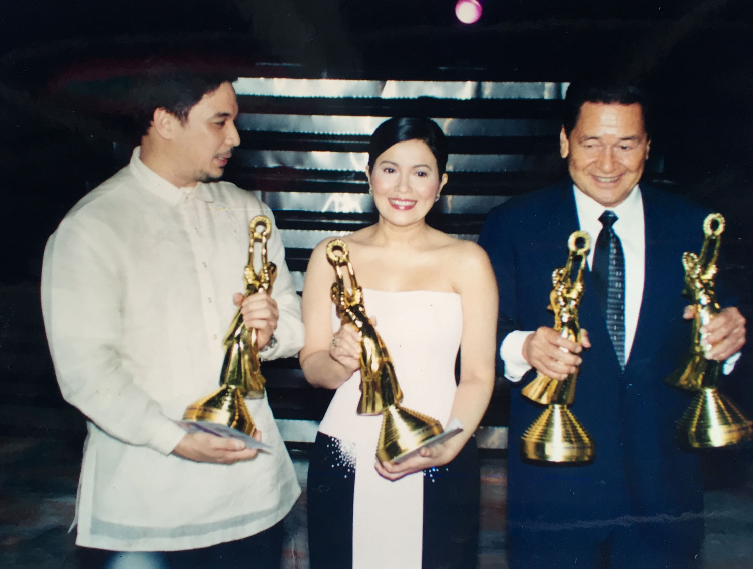 With Ricky Davao and Lorna Tolentino, Eddie Garcia holds his two FAMAS statuettes, one for best supporting actor in  Ito Ang Pilipino  and the other for best actor in  Pinagbuklod ng Langit , both 1969 movies.