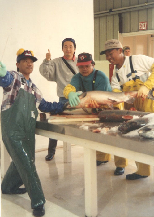 "The Butching Crew at South Naknek Cannery. Benji Uclaray is on the far left, and his nephew Angel Uclaray Jr. is on the far right holding the salmon. The fellow giving the ""thumbs up"" worked for TK, the Japanese company that packed the salmon roe. The group was butchering the king salmon, which are too large to be processed by the machines. (Photo by Katherine Ringsmuth, 1988)"