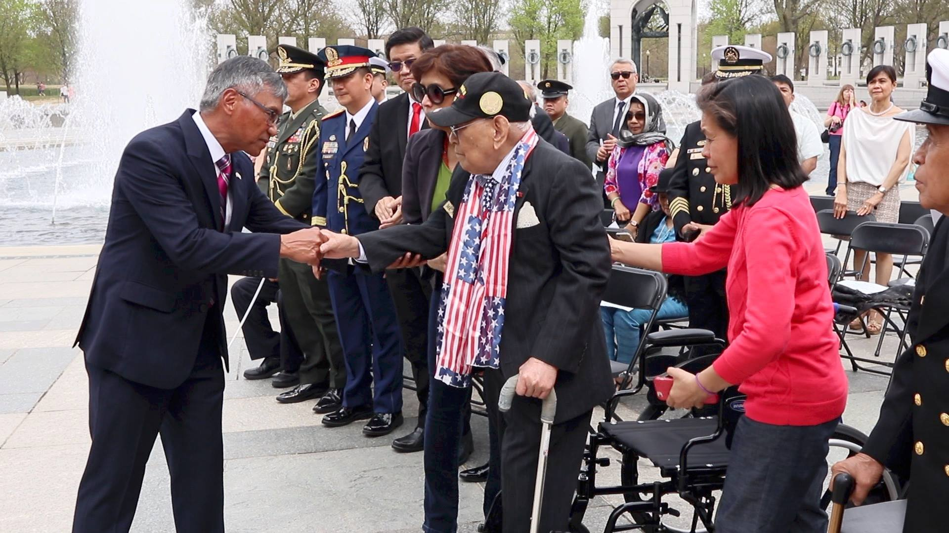 Maj. Gen. Antonio Taguba, a son of a Filipino World War II veteran, shakes the hand of 101-year-old Celestino Almeda, the oldest living Filipino veteran in the Washington DC area, during the Bataan Day commemoration at the National World War II Memorial. (Photo by Bing Branigin)