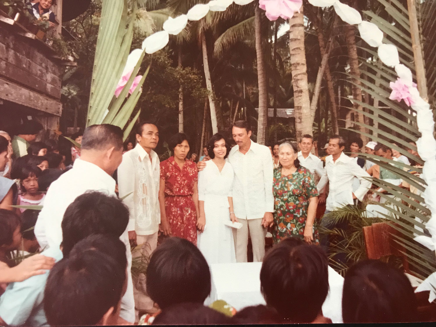 As a divorcee, my dad could not be married in the Catholic Church. Here, they stand center at their wedding ceremony in the front yard of my childhood home. My mom holds my Grandma Inega's hand.