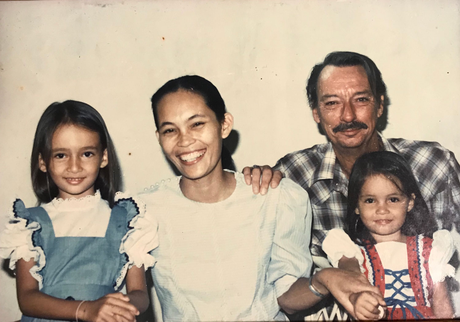L-R: My sister Shelley, Mom, Dad, and me. This was taken in a studio in Manila before we moved to the U.S. for the first time. It is our only family portrait.