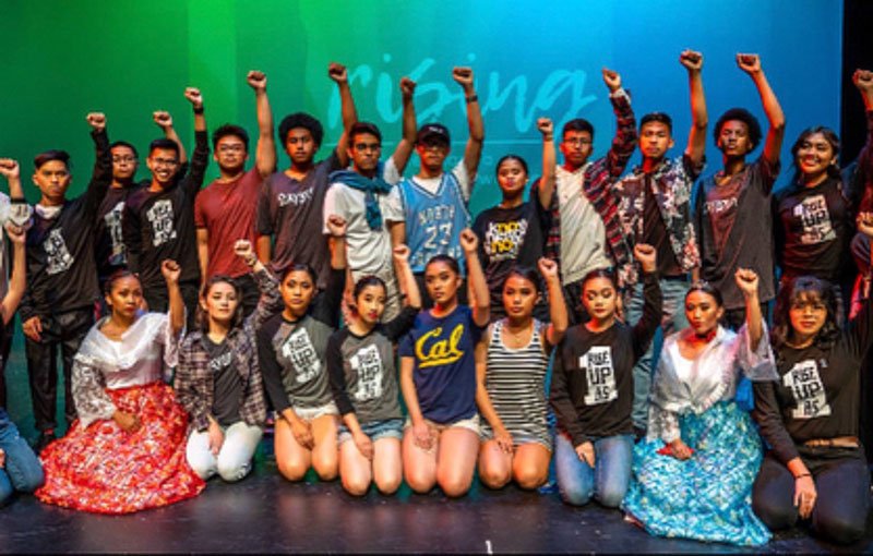 "LMASP and ""Us"" History students get ready for the 2018 showcase titled ""Rising."" They pose with a fierce look on their faces with fists in the air that refuse to back down. Photo by Doug Villalos."