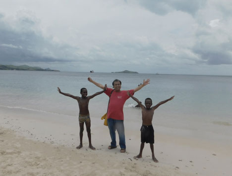 The author poses with locals on a beach in Port Moresby, Papua New Guinea. (Photo by Rey E. de la Cruz)