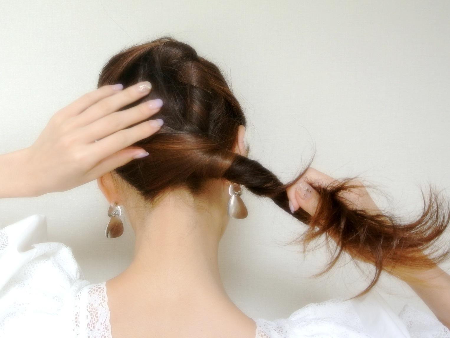 ②その毛先を巻き込むようにして残り全体のヘアをねじってまとめます。