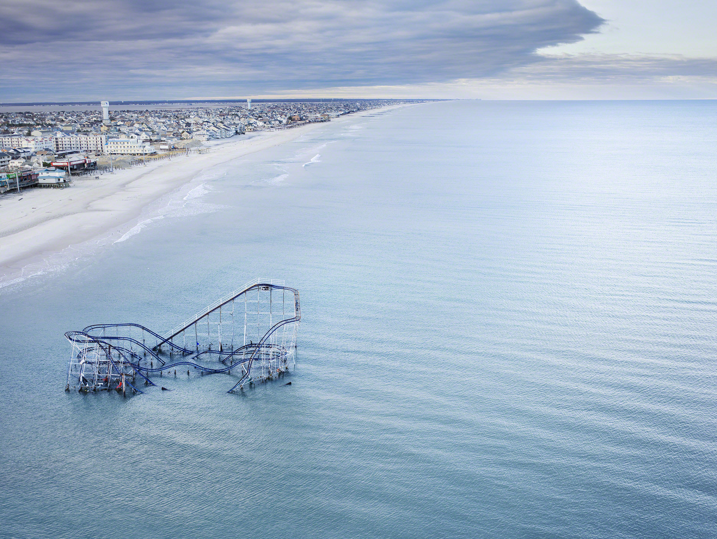 The roller coaster from the boardwalk in Seaside Heights, New Jersey partially submerged in theocean after Hurricane Sandy. © Stephen Wilkes courtesy of Peter Fetterman Gallery.