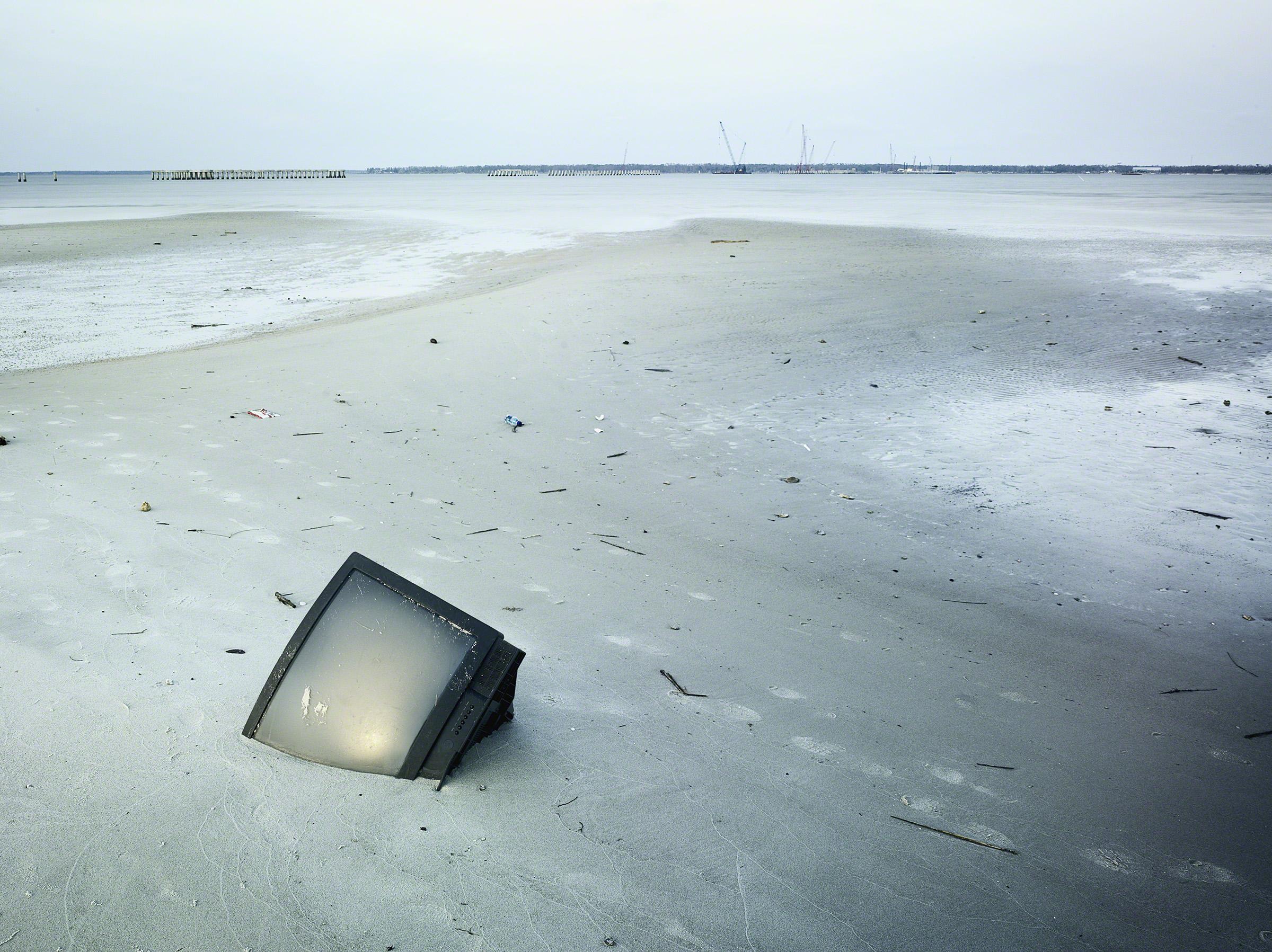 TV in the sand post Hurricane Katrina, Bay St. Louis, Mississippi. © Stephen Wilkes courtesy ofPeter Fetterman Gallery.