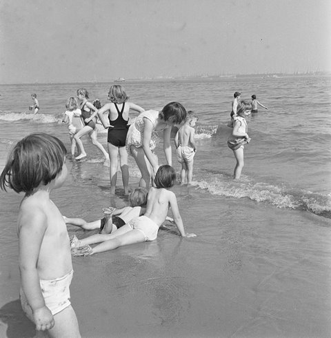 """Children playing in the sea at New Brighton  """"We'd all be sitting on the sand and we'd go in the water, but not too far out, just a paddle.""""Betty Jamieson, Kensington Fields Community Association"""