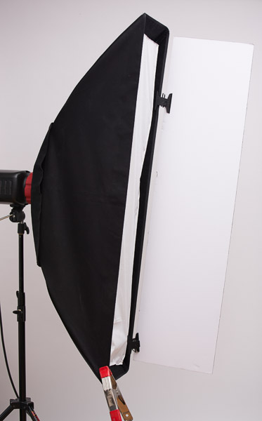 Barn doors don't have to be restricted to only working with small lights and hard reflectors. I also use the Mulit-Clips and foamcore to create barn doors for my softboxes and strip ights to help control light from spilling into areas where I don't want it. Here I show a barn door solution for use with my  Westcott strip box **. The spring clamp is there to balance the weight of the foamcore so the box doesn't spin in its speedring.