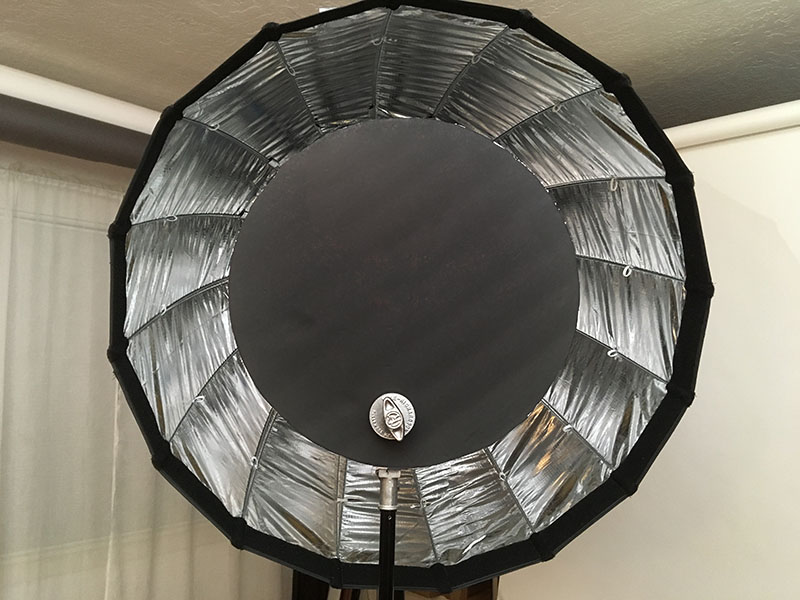 Black foam-core disk blocking the center of the deep parabolic softbox
