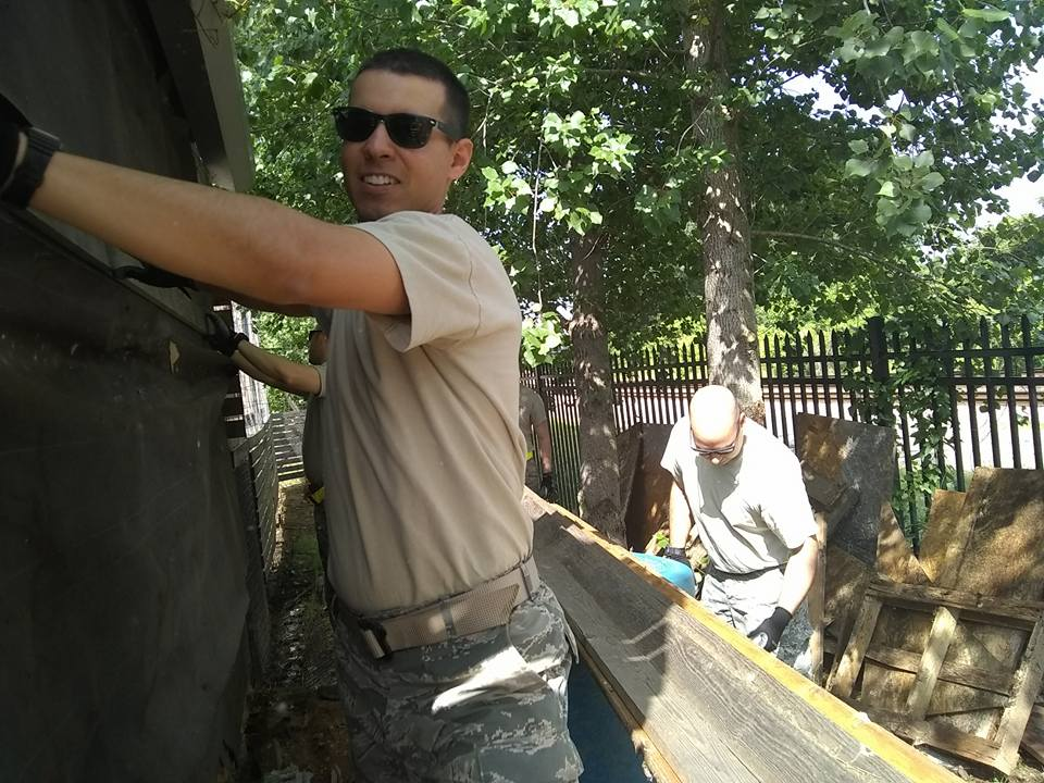 Volunteers from Maxwell Air Force Base finish the siding on the chicken coop.