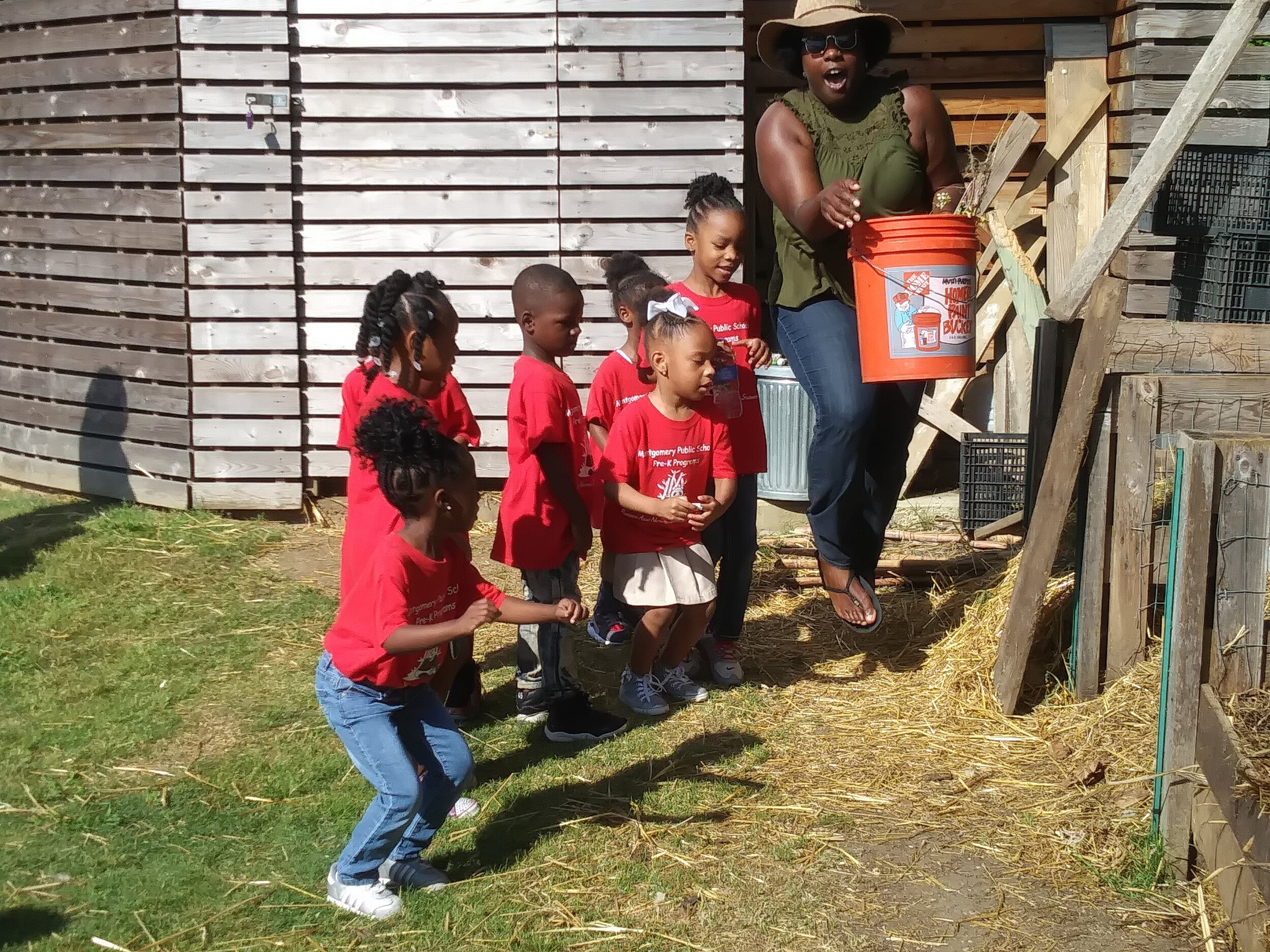 E.A.T. South board member Natilee McGruder teaches children about compost.