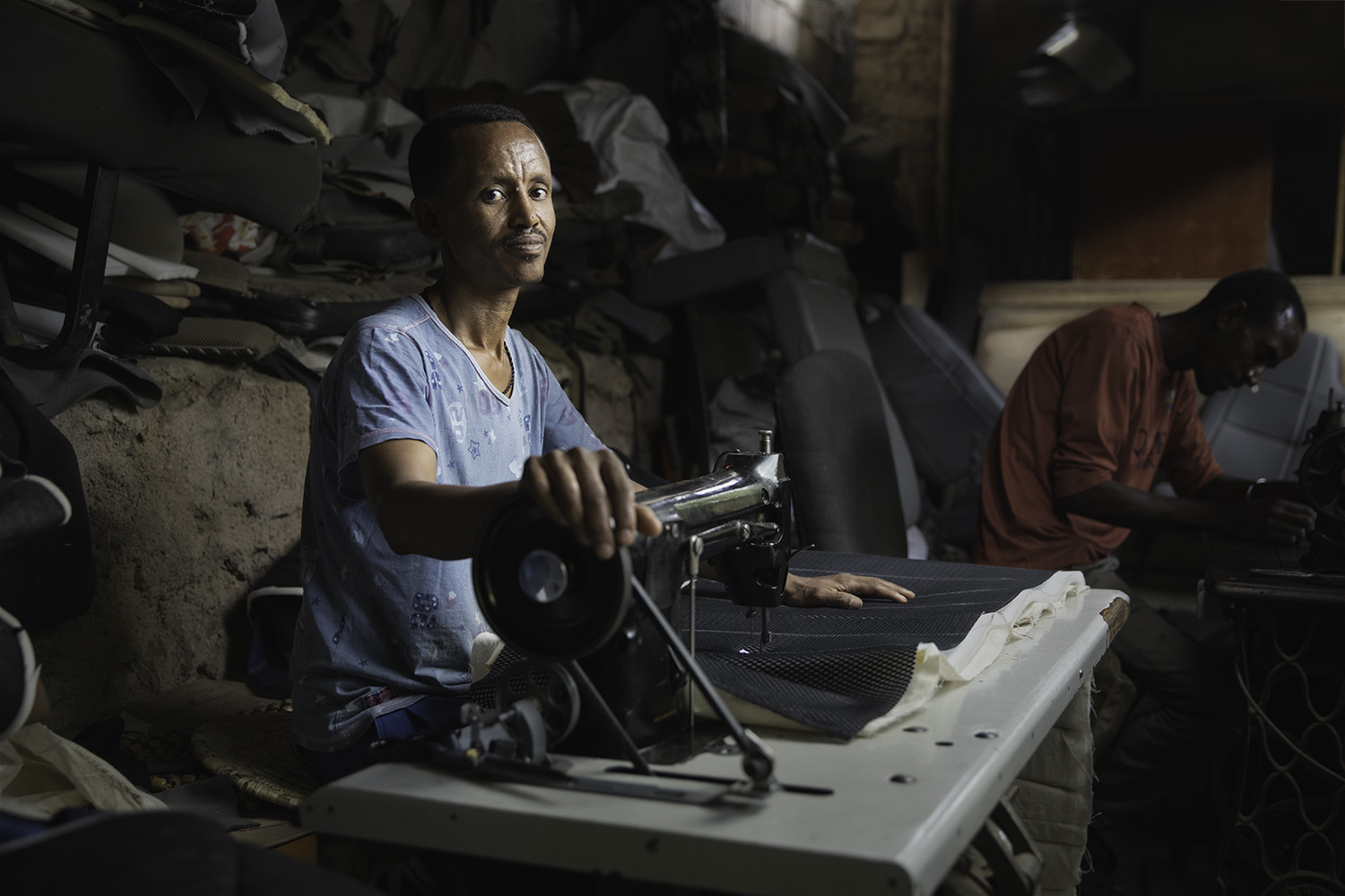 Man sitting a sew machine in upholstery shop in Ethiopia