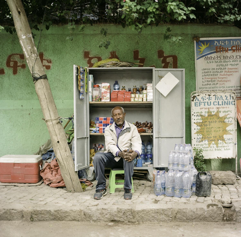 Older Ethiopian sitting outside cabinet selling food