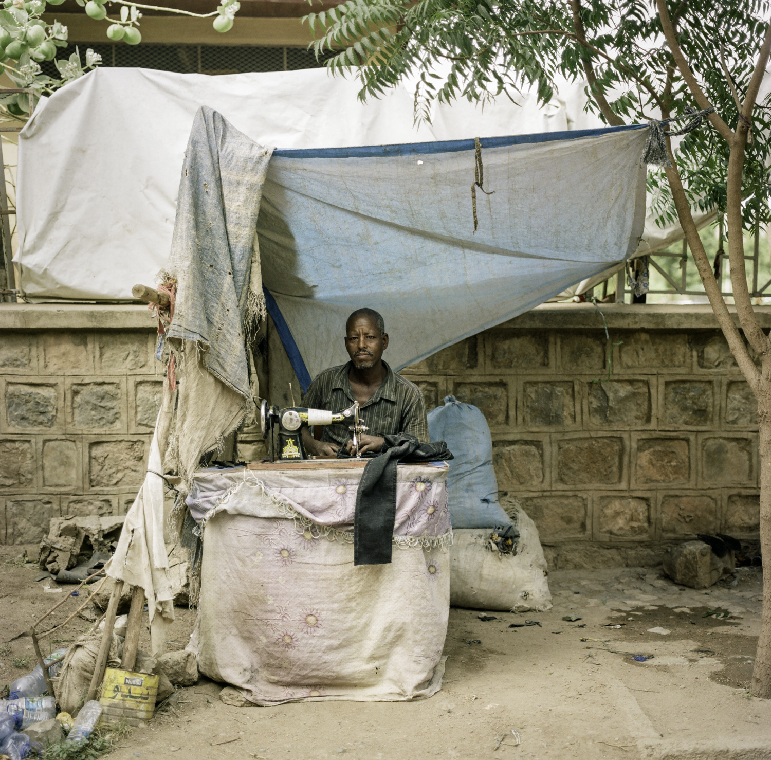 Ethiopian sewing clothes under shade.