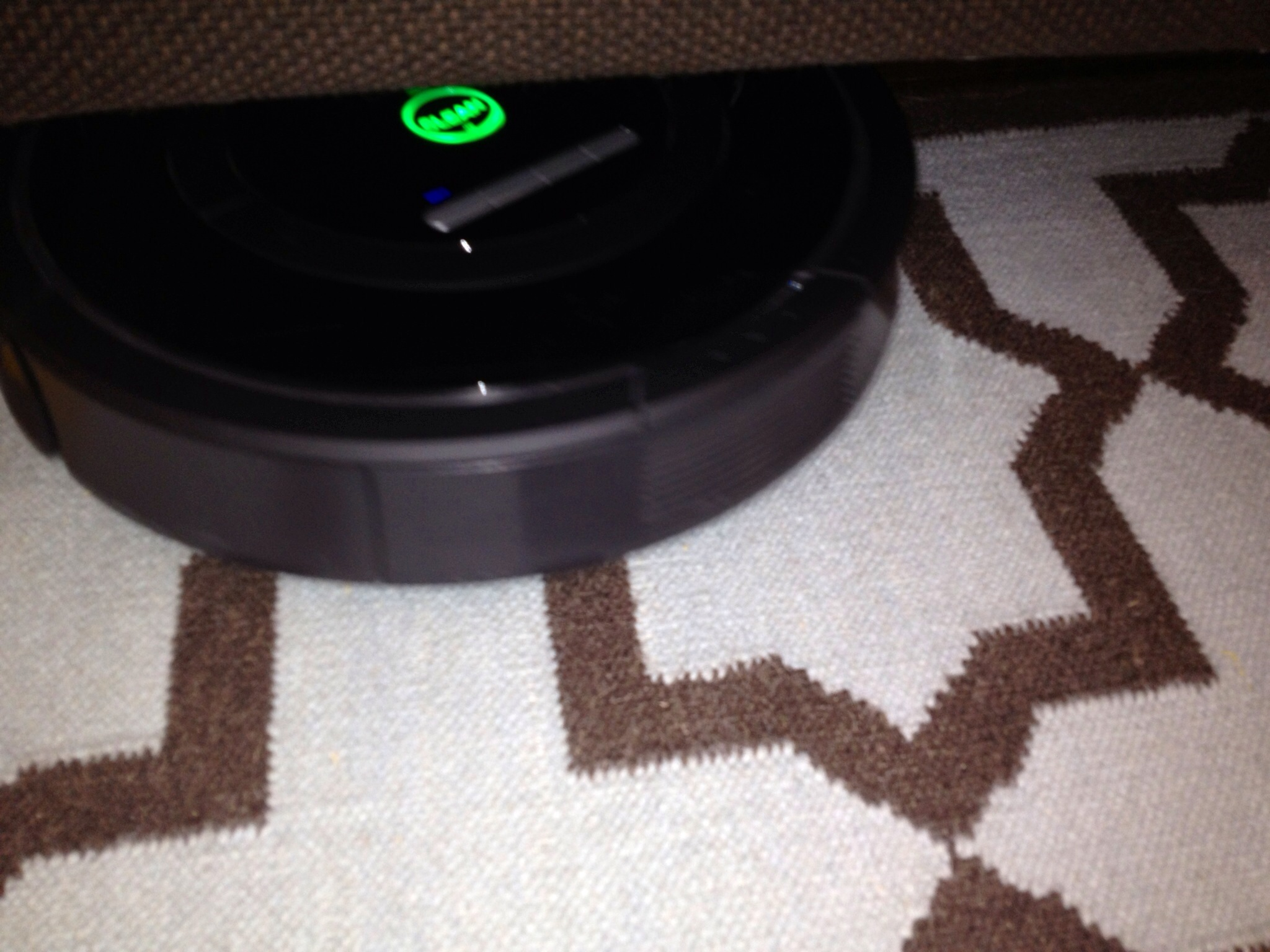 The Roomba is finding its way under the couch.