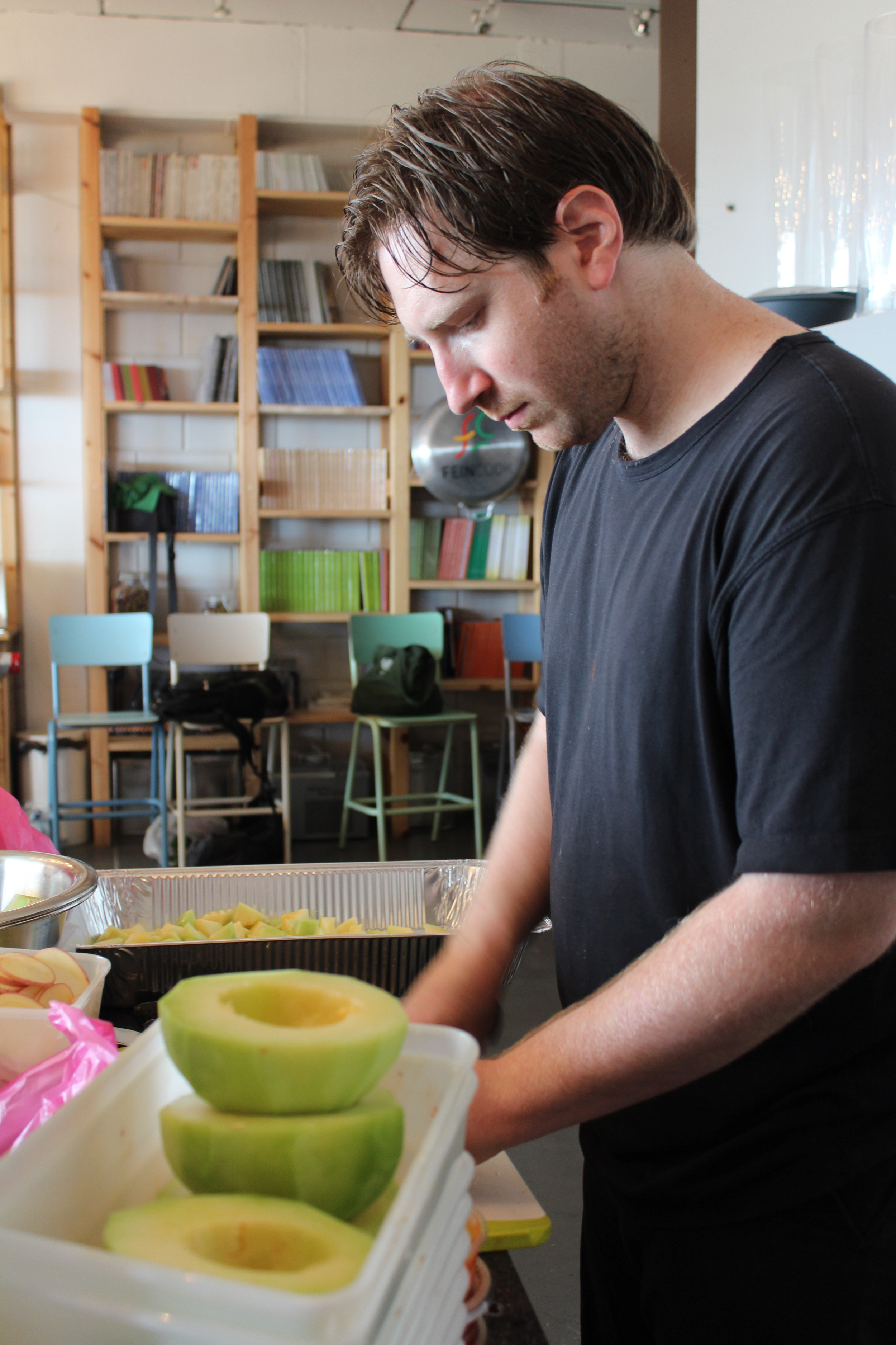 Jason Marcus shaving melons in preparation for a melon salad dish he is creating on his visit in Tel Aviv