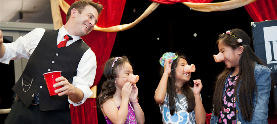 Bay Area entertainer and magician Dante on stage with some smiling children.