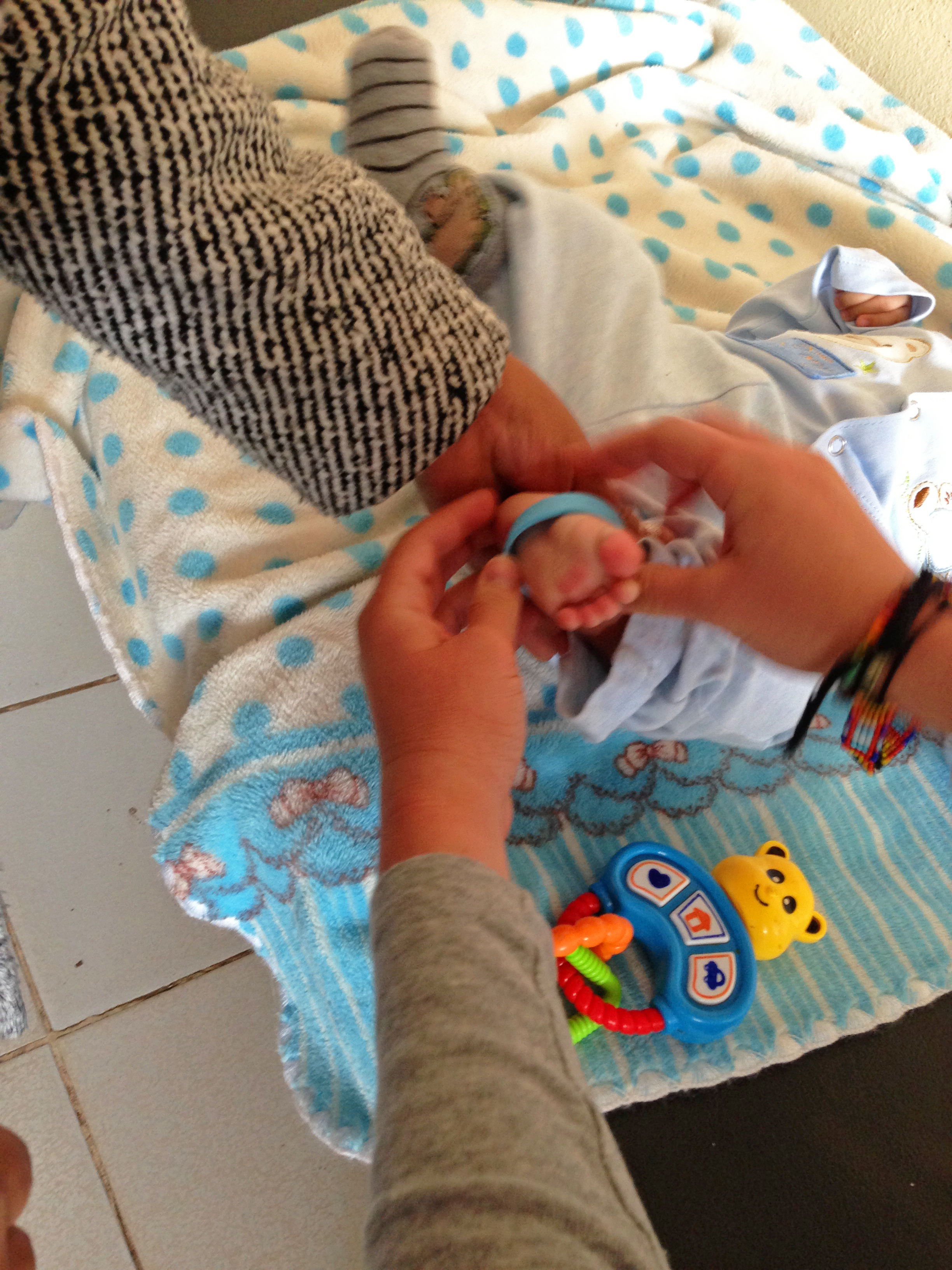 Putting a bracelet on a 2-month-old's ankle. Photo taken: June 1, 2013.