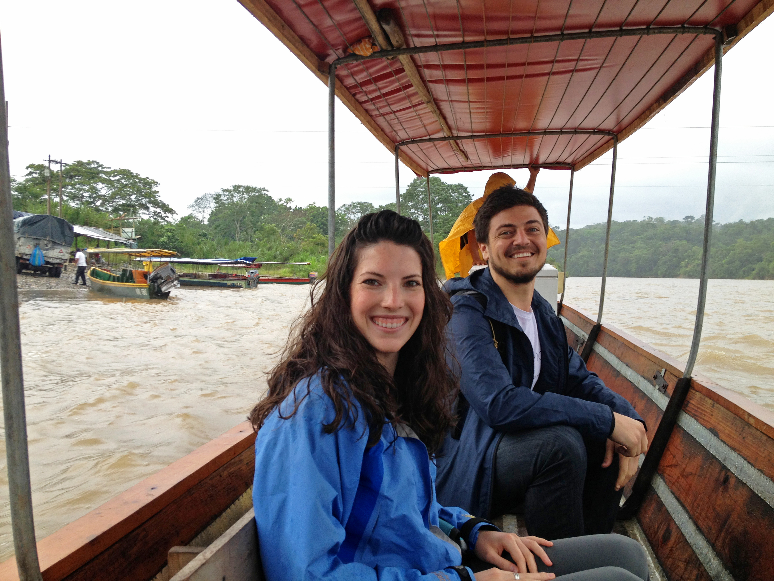 """To get to one of the four clinics we're working at in rural Ecuador, Lauren Braun, our founder and President, and Alex Bozzette, our Ecuador Project Coordinator, and Trish Braun, our VP (not pictured), had to take this long boat across a river during a rainstorm as it's the only way to reach this clinic. Our Ministry of Public Health partners brought along a vaccine refrigerator that had been repaired for this clinic, and several iceboxes full of vaccines. This trip highlighted for us a few of the many challenges to maintaining vaccines in a hot, humid, rural environment. When we told them how amazed we were at their dedication to keeping these hard-to-reach people healthy, and they said """"We're just doing our job."""" Photo taken: June 14, 2013."""