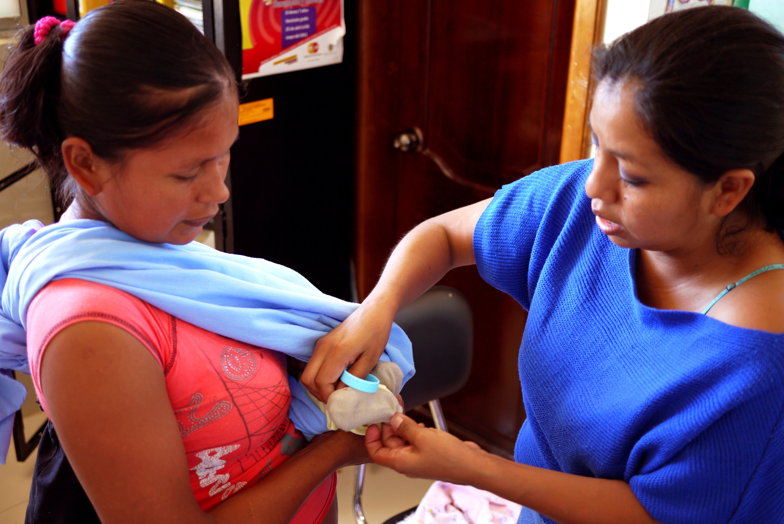 Guadalupe (right), a local vaccine expert in Ecuador, puts a bracelet on this mother's infant to help his mom remember when to return to this clinic for the next vaccination appointment. Photo taken: June 25, 2013.