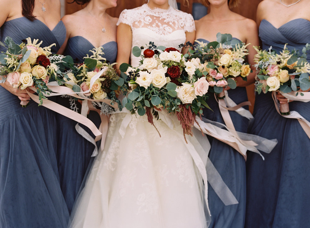 The bride poses with her bridesmaids and beautiful floral arrangements just before her wedding at Cheekwood Botanical Garden & Museum of Art in Nashville, TN. Weddng, design, and flor arrangements by Big Events Wedding.