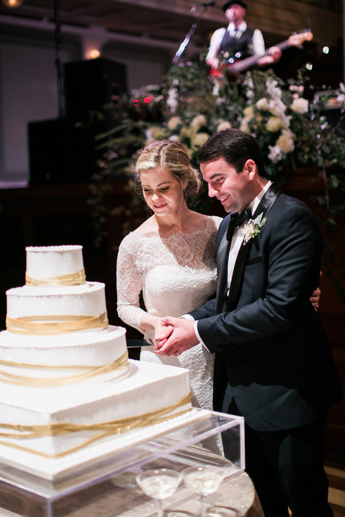 The newly wedded Browns cut their beautiful wedding cake at theit Schermerhon Symphony Center wedding reception in Nashville, TN. Wedding planning & design by Big Events Wedding.