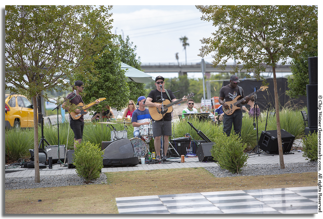 Forrest Hoffar and the Feels are partially obscured by trees as they play on the lawn at Armature Works. These guys stood out in the sun for hours entertaining. Come on Armature Works, help some brothers out!